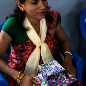 Teacher of the tailoring group with the gift given by the trainees